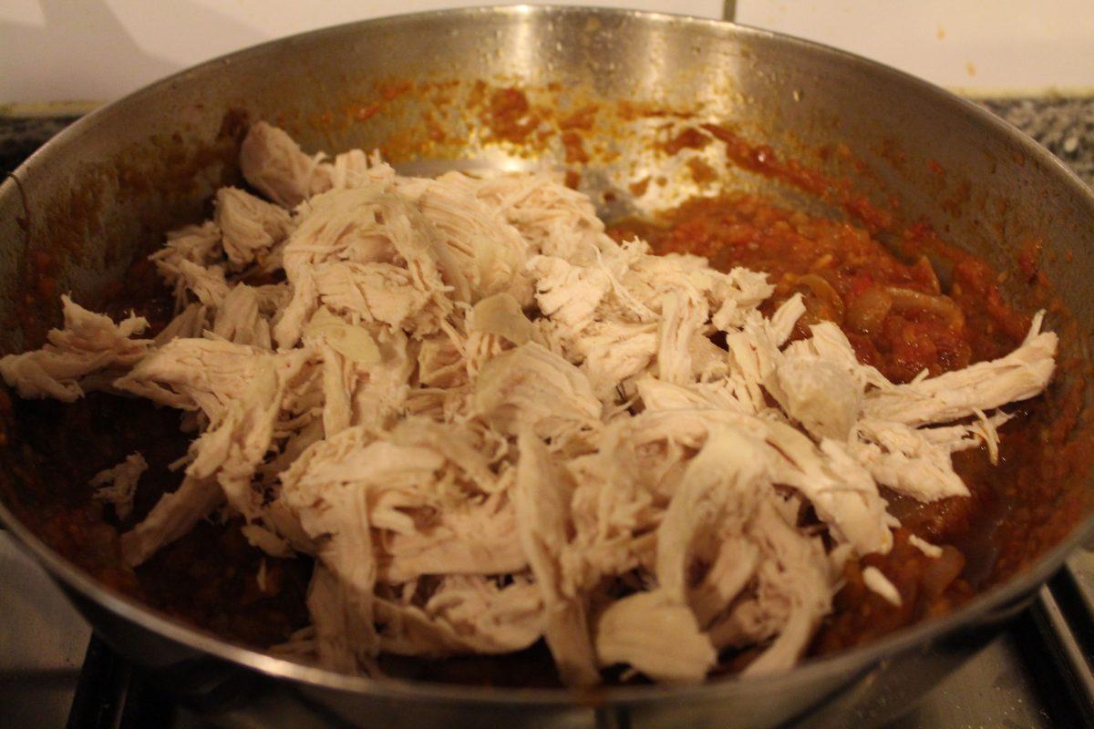 מוסיפים את העוף המפורר לרוטב העגבניות