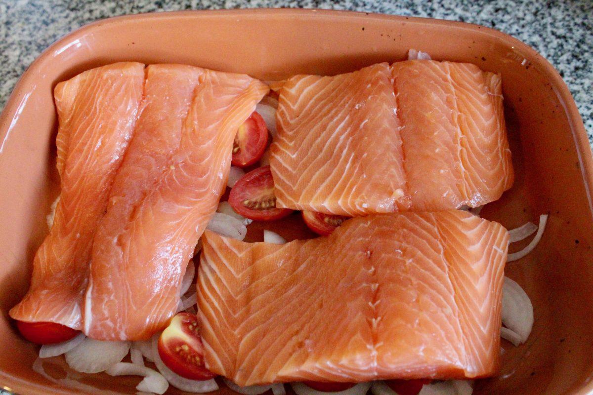 מניחים את הדג על הבצל והעגבניות